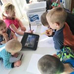 6 young siblings sit around a tablet learning together